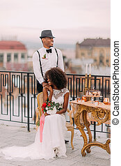 Happy african newlyweds smiling on the terrace