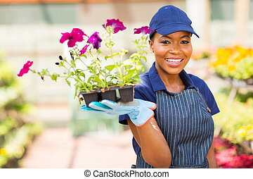 african nursery worker holding flowers