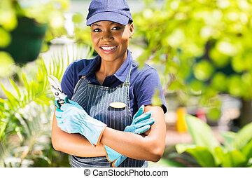 african nursery worker holding garden tool