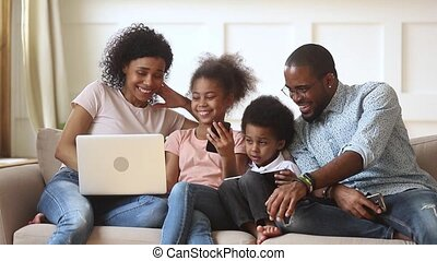 Happy african parents and children using devices together on...