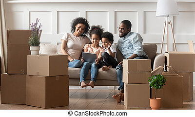 Happy african parents and children using tablet on moving day