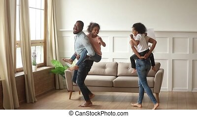 Happy african parents piggyback kids laughing playing at home