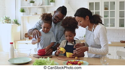 Happy african parents teaching kids cutting salad cooking in kitchen