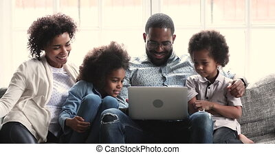 Happy african parents with two kids watching videos using notebook