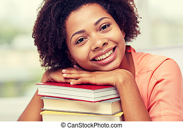 happy african student girl with books at home