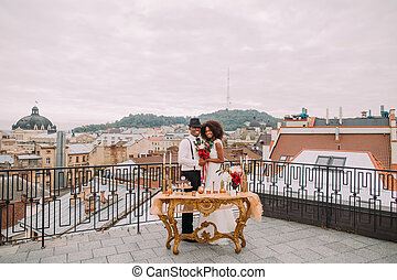Happy african wedding couple posing for camera on the terrace