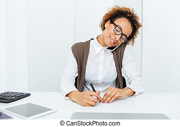 Happy african woman accountant talking on cell phone and writing