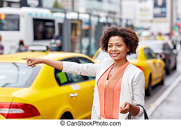 happy african woman catching taxi