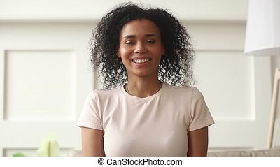 Happy african woman doing video chat calling looking at camera