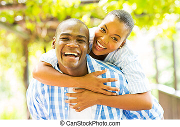 african woman enjoying piggyback ride on boyfriend - happy...