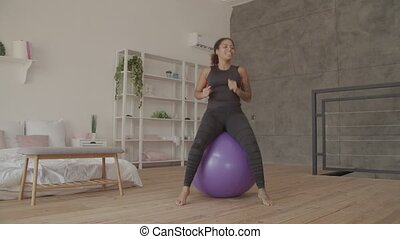 Happy african woman exercising on fitball indoors