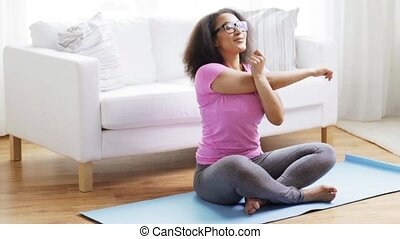 happy african woman exercising on mat at home - fitness,...