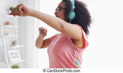 happy african woman in headphones dancing at home