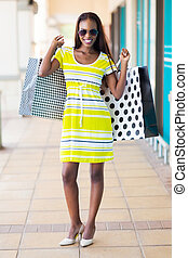 happy african woman in shopping mall