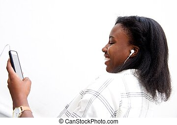 Happy african woman listening music on mobile
