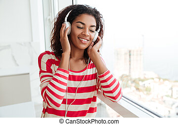 Happy african woman listening to music from her smartphone