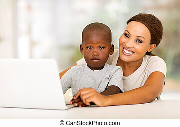 african woman relaxing at home with her little boy