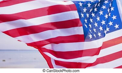 happy african woman with american flag on beach -...