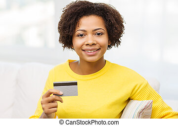 happy african woman with credit or debit card - people,...
