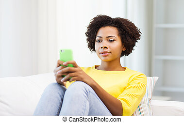 happy african woman with smartphone at home