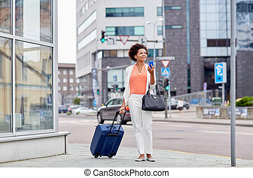 happy african woman with travel bag and smartphone - travel,...