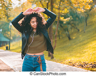 Happy african young woman with curly hair listening to music on earphones. Hispanic hipster girl dancing to rhythm and singing along melody in the autumn park.