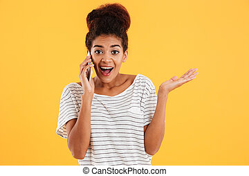 Happy african young woman with open mouth talking on phone isolated