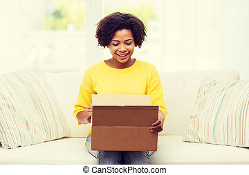 happy african young woman with parcel box at home - people, ...
