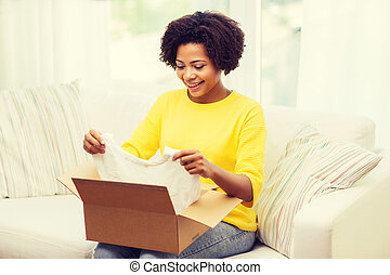 happy african young woman with parcel box at home - people,...