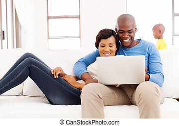 afro american couple using laptop at home