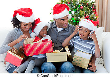 Happy Afro-American family playing with Christmas presents