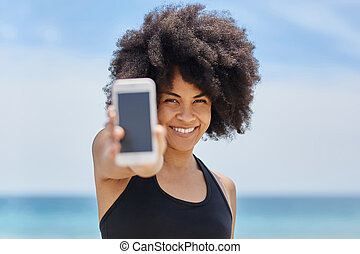 Happy afro american girl holding smartphone
