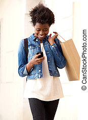 Happy afro american girl looking at cell phone with shopping bag