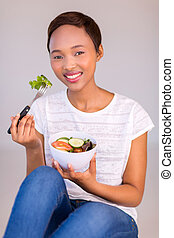 afro american woman eating green salad