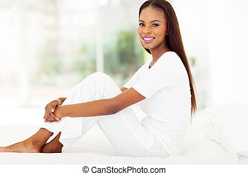 afro american woman sitting on bed