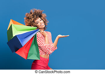 Happy afro girl holding colorful shopping bags.