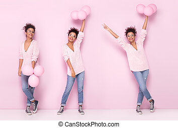 Happy afro girl with amazing smile posing on pink background.