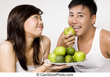 Happy Again! - A young asian male happily eats a green apple...