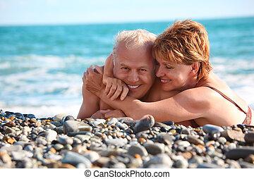 happy aged pair lie on pebble beach, focus on woman
