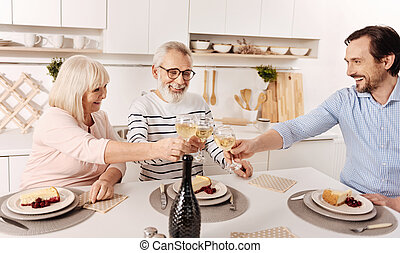 Happy aged parents celebrating holiday with son at home