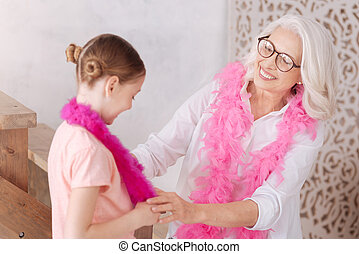 Happy aged woman looking at her granddaughter