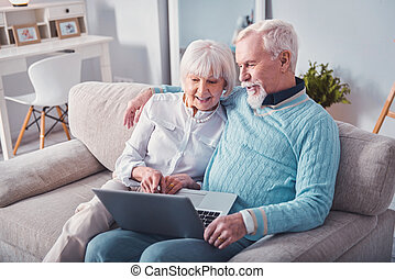 Happy aging couple watching photos on the laptop