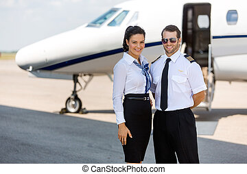 Happy Airhostess And Pilot Standing Against Private Jet -...
