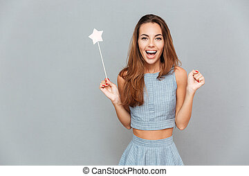 Happy amazed young woman holding magic wand over grey...