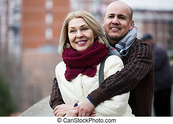 mature woman and elderly man posing together outdoors