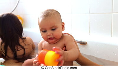 Happy and baby and her sister bathing and playing together in a white bathtub. Adorable young siblings playing in bathtub with their mother. Bath time for babies