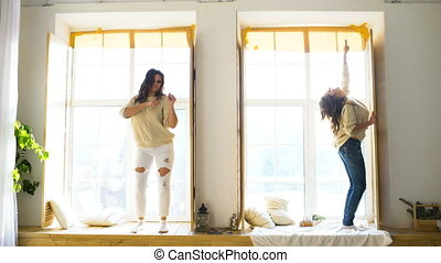 Happy and beautiful girlfriends dance on window having fun and joy in bedroom