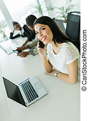Happy and beautiful young businesswoman sitting at an office table and talking on her cell phone