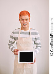 Happy and confident male cafe worker in apron smiling at a camera, standing with digital tablet showing screen.