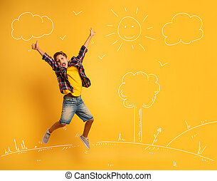 Happy and emotional child jumps over a yellow background.